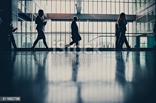 905689676 istock photo Businesspeople walking in busy office building 511652736