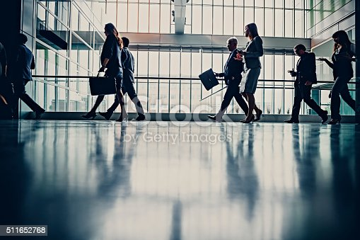 905689676 istock photo Businesspeople walking in busy office building 511652768
