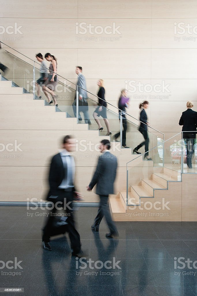 Businesspeople walking on busy office staircase stock photo