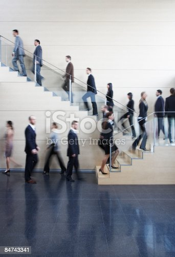 84743203 istock photo Businesspeople walking on busy office staircase 84743341