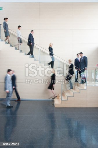 84743203 istock photo Businesspeople walking on office staircase 483635929