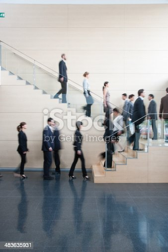 84743203 istock photo Businesspeople walking on office staircase 483635931