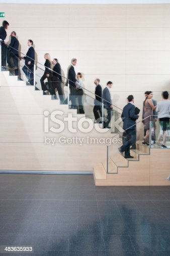 84743203 istock photo Businesspeople walking on office staircase 483635933