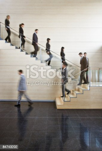 84743203 istock photo Businesspeople walking on office staircase 84743202