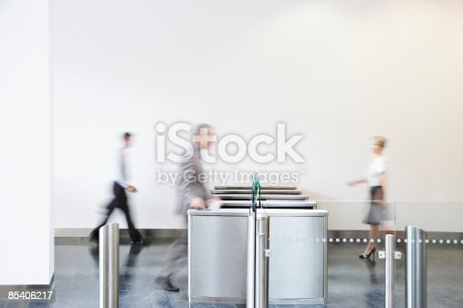 istock Businesspeople walking through turnstile 85406217