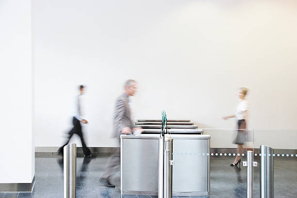 businesspeople walking through turnstile - terugkomen stockfoto's en -beelden