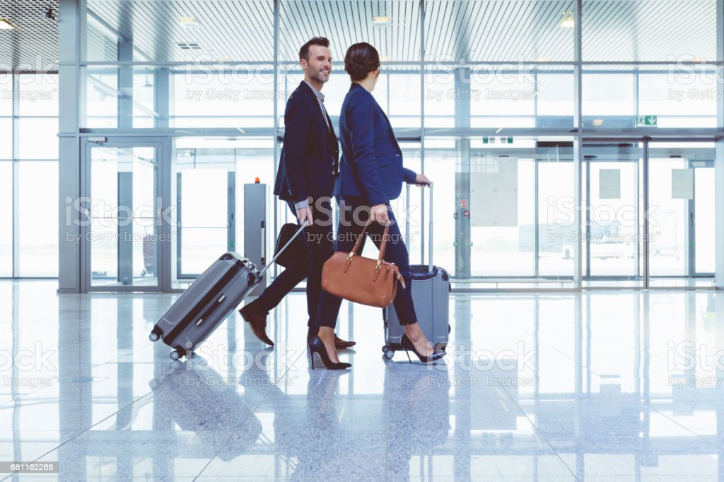 Businesspeople walking with luggage inside airport terminal stock photo