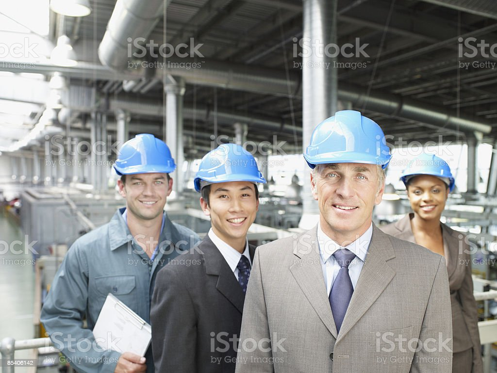 Businesspeople wearing hard-hats in factory royalty-free stock photo