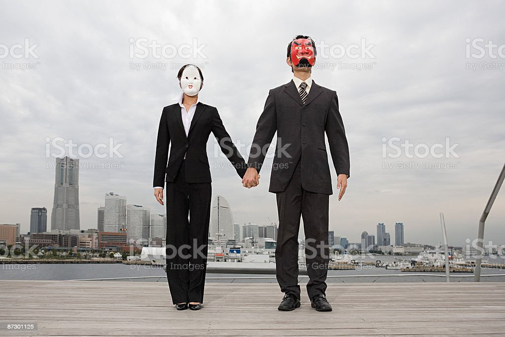 Businesspeople wearing masks holding hands royalty-free stock photo