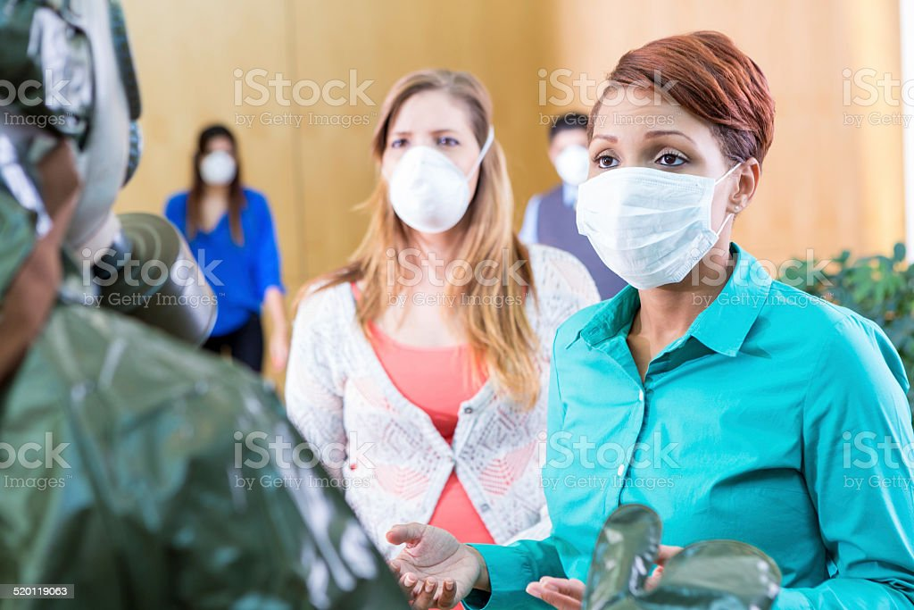 Businesspeople wearing protective masks talking with person in hazmat suit stock photo