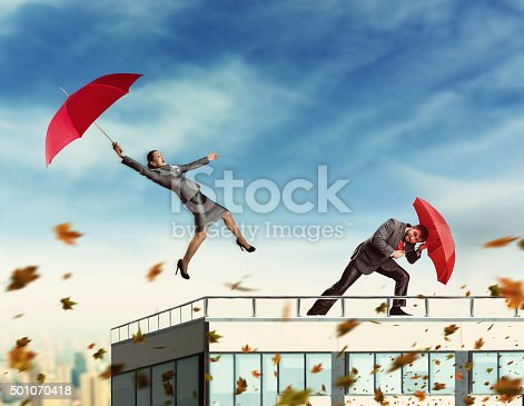 Businesspeople with umbrellas on the skyscraper while storming