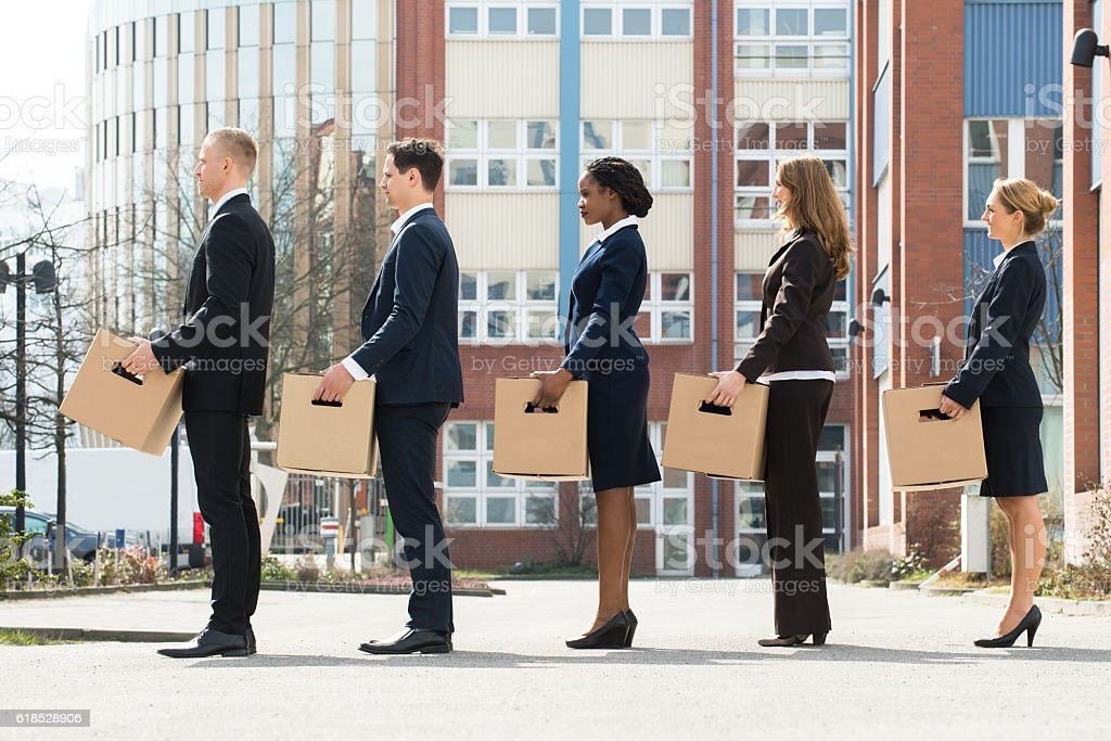 Businesspeople With Boxes Standing In A Line stock photo