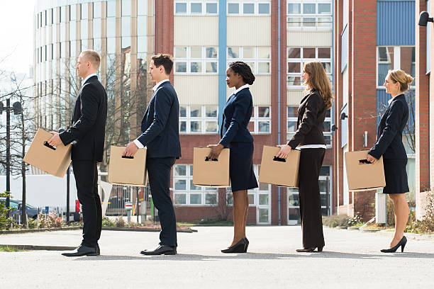 Businesspeople With Boxes Standing In A Line Group Of Multiracial Businesspeople With Cardboard Boxes Standing In A Line  downsizing unemployment stock pictures, royalty-free photos & images