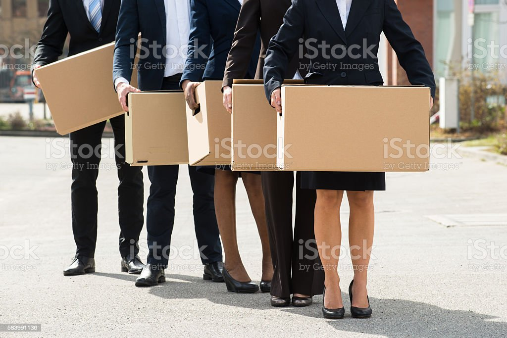 Businesspeople With Cardboard Boxes Standing In A Line stock photo