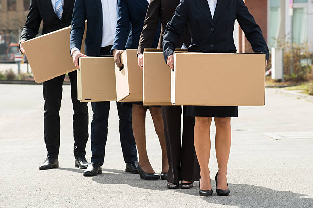 Businesspeople With Cardboard Boxes Standing In A Line Close-up Of Businesspeople With Cardboard Boxes Standing In A Line;Outdoor downsizing unemployment stock pictures, royalty-free photos & images