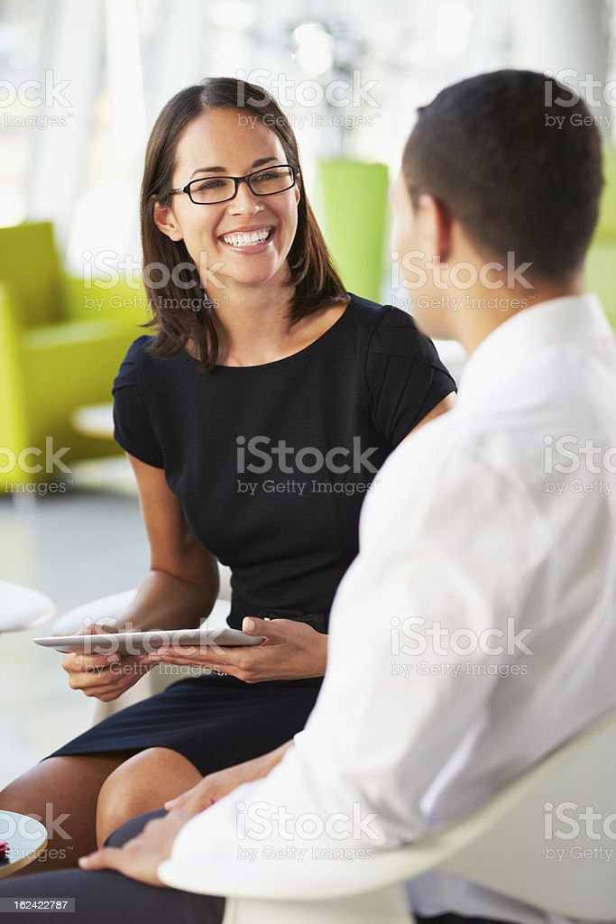 Businesspeople With Digital Tablet Having Meeting In Office stock photo