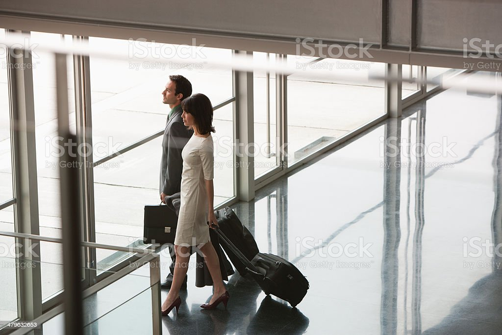 Businesspeople with suitcases leaving building stock photo