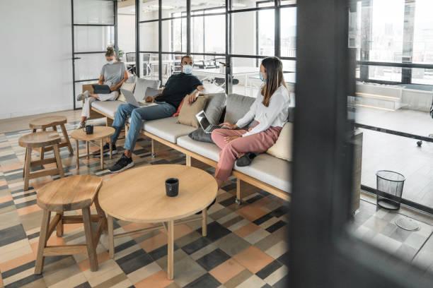 Geschäftsleute, die auf einem Sofa in einem modernen Büro arbeiten und soziale Distanz pflegen – Foto