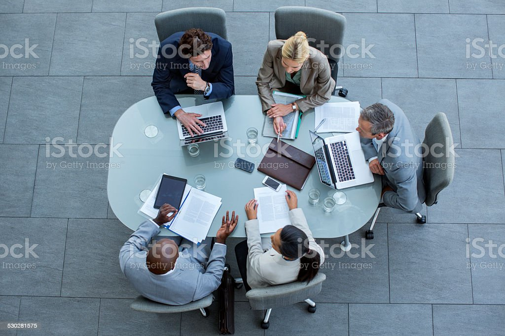 Businesspeople working at conference table High angle view of business professionals discussing strategy at conference table in office 25-29 Years Stock Photo