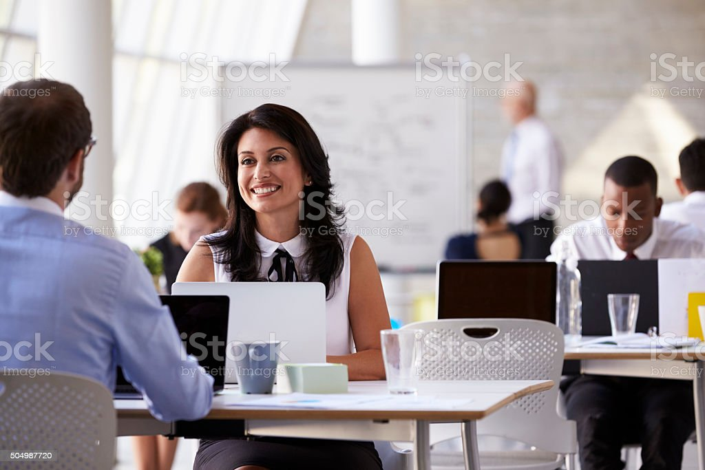 Businesspeople Working At Desks In Modern Office Businesspeople Working At Desks In Modern Office 20-29 Years Stock Photo