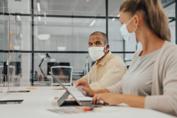 Geschäftsleute, die im Büro mit Glastrennwand arbeiten, die sie teilen – Foto