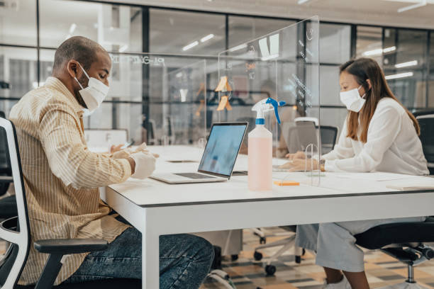 Businesspeople working at office with glass partition dividing them stock photo