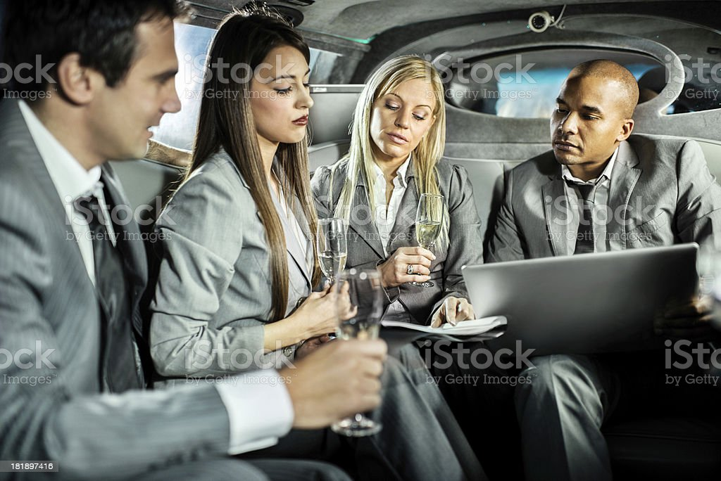 Businesspeople working in a limousine and drinking champagne royalty-free stock photo