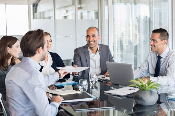 Businesspeople working in meeting Business man passing over documents to leader during meeting. Businessman passing necessary agreement to the business partner in conference room. Group of businessmen and businesswomen working together. staff meeting stock pictures, royalty-free photos & images