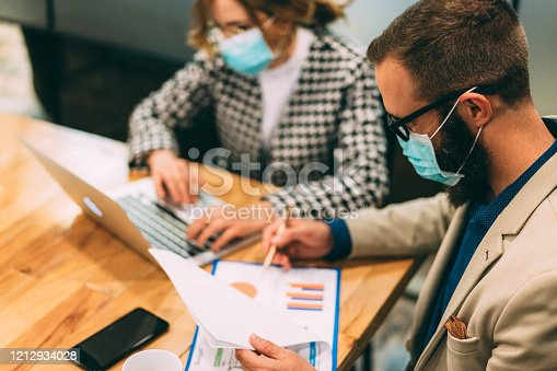 Businesspeople wearing masks in the office for safety during COVID-19 pandemic