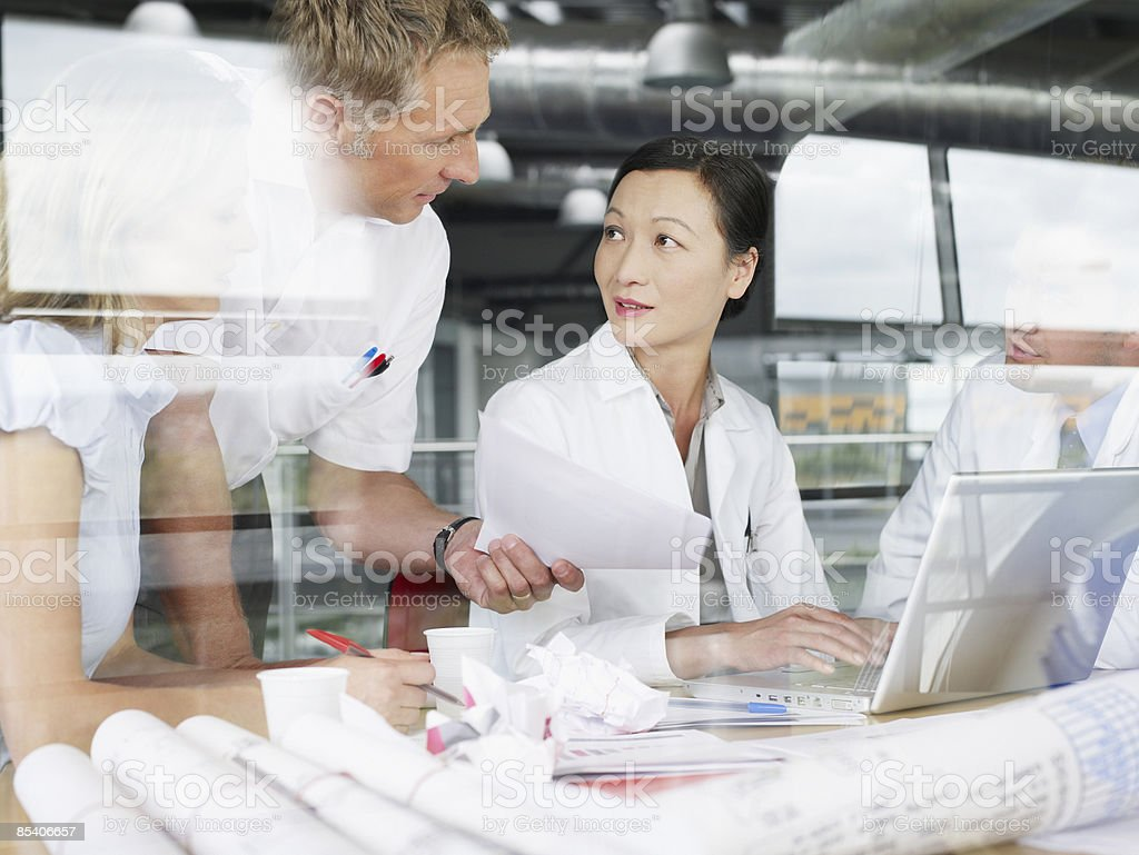 Businesspeople working on laptop and blueprints royalty-free stock photo