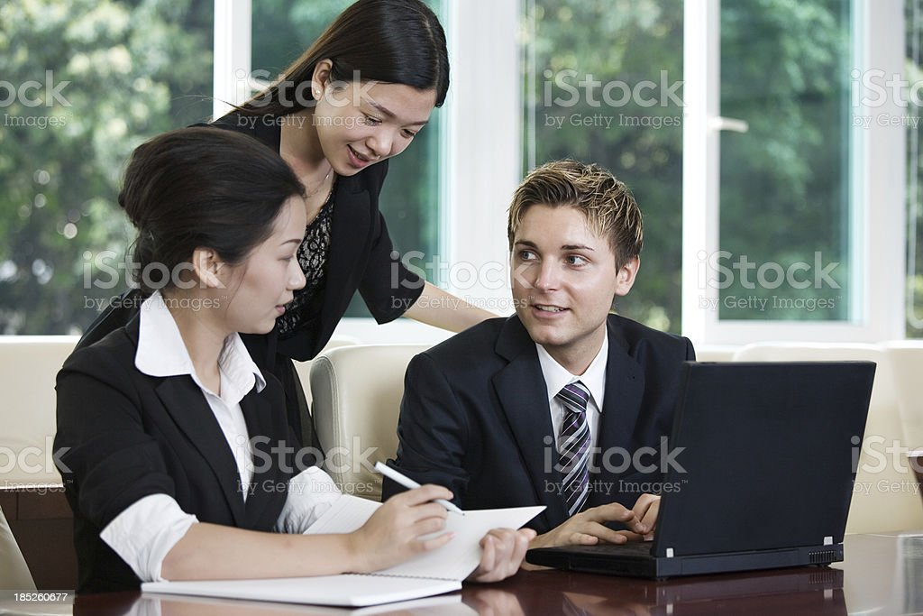 Businesspeople working on laptop in an office stock photo