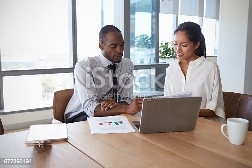 istock Businesspeople Working On Laptop In Boardroom Together 677893494