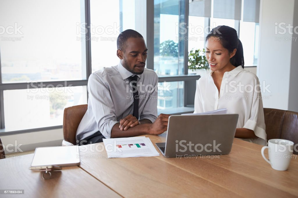 Businesspeople Working On Laptop In Boardroom Together stock photo