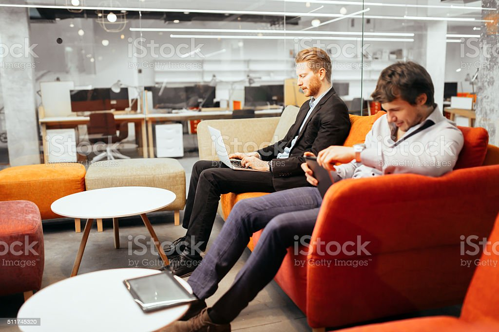 Businesspeople working while looking at devices stock photo