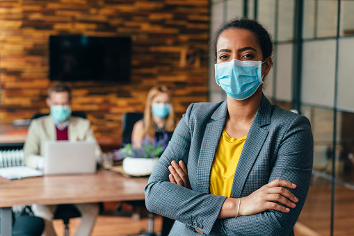 Businesspeople wearing masks in the office for safety during COVID-19 pandemic, mixed race businesswoman looking at camera