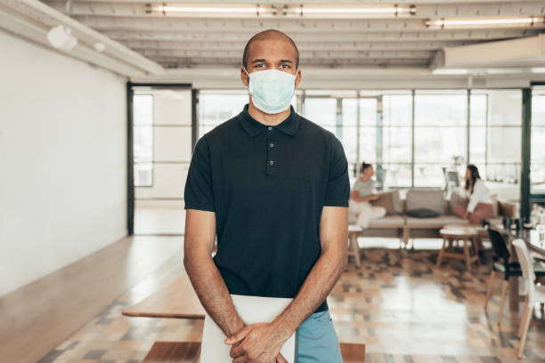 Businesspeople working with face masks in the office during COVID-19 pandemic stock photo