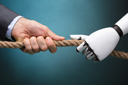 istock Businessperson And Robot Playing Tug Of War 924555512
