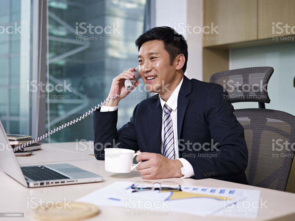 Businessperson at desk talking on phone stock photo