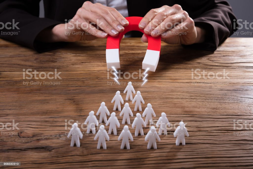Businessperson Attracting Human Figures With Horseshoe Magnet stock photo