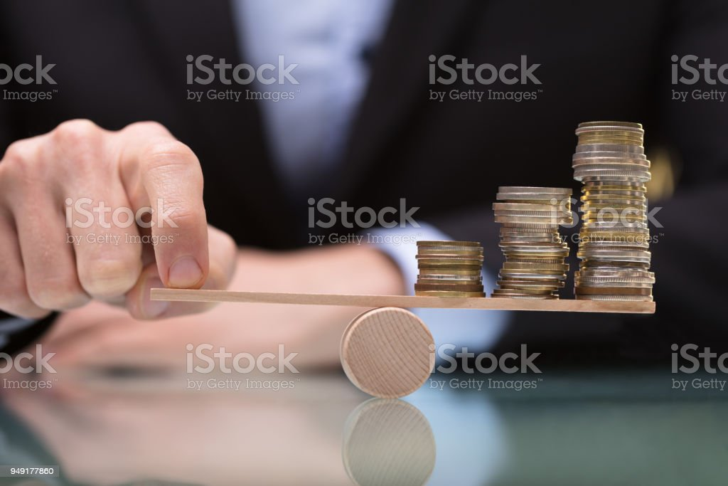 Businessperson Balancing Stacked Coins On Seesaw stock photo