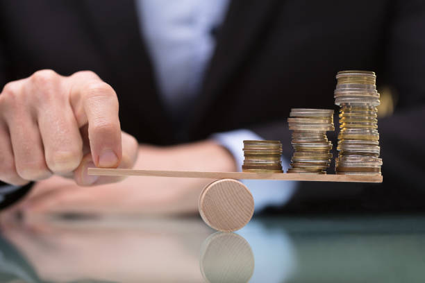 businessperson balancing stacked coins on seesaw - balance foto e immagini stock