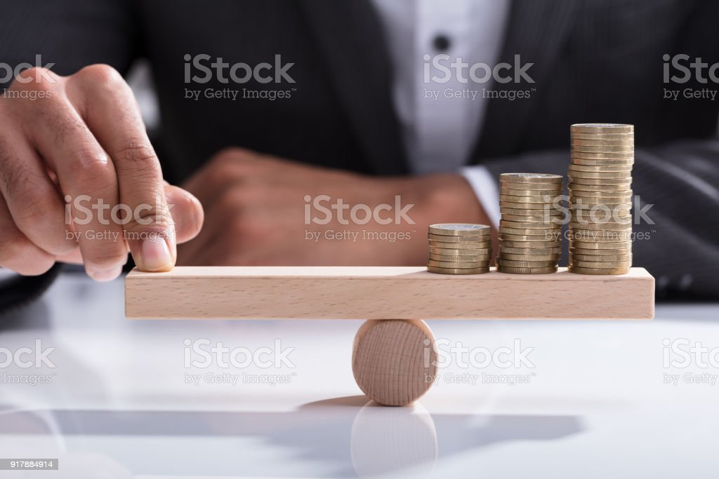 Businessperson Balancing Stacked Coins On Wooden Seesaw stock photo