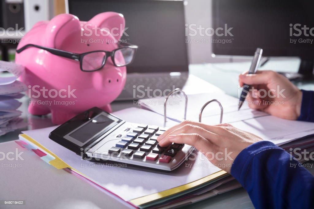 Businessperson Calculating Bill With Calculator stock photo