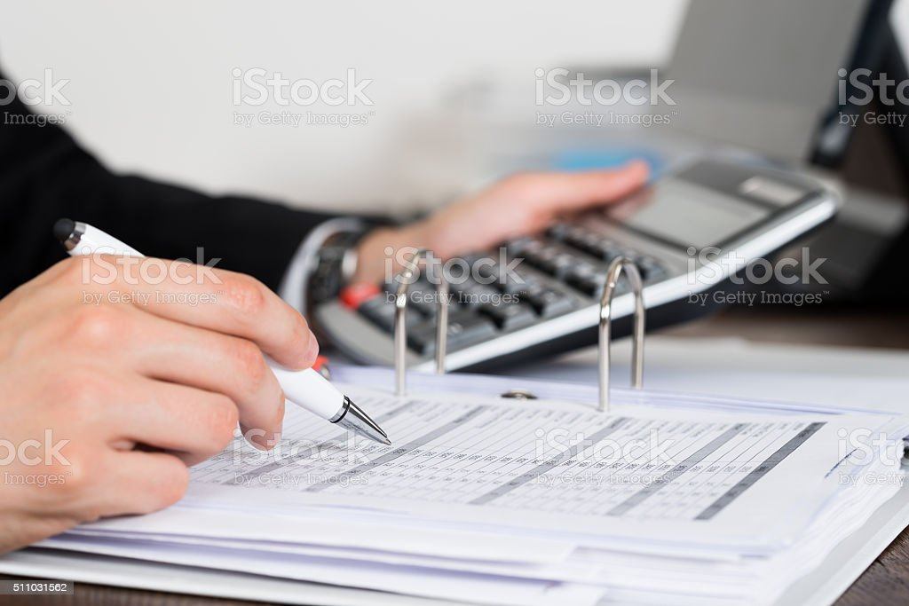 Businessperson Calculating Invoice In Office stock photo