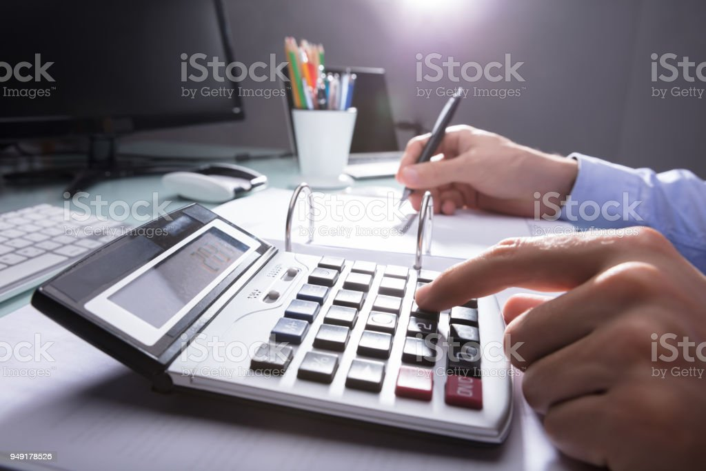 Businessperson Calculating Receipt With Calculator stock photo