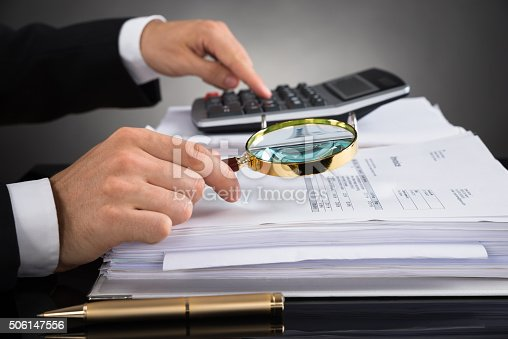 istock Businessperson Checking Invoice With Magnifying Glass 506147556
