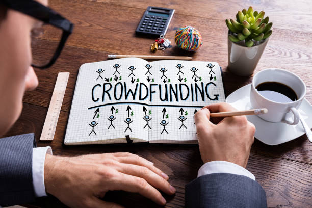 Businessperson Drawing Crowdfunding Concept On Notebook stock photo