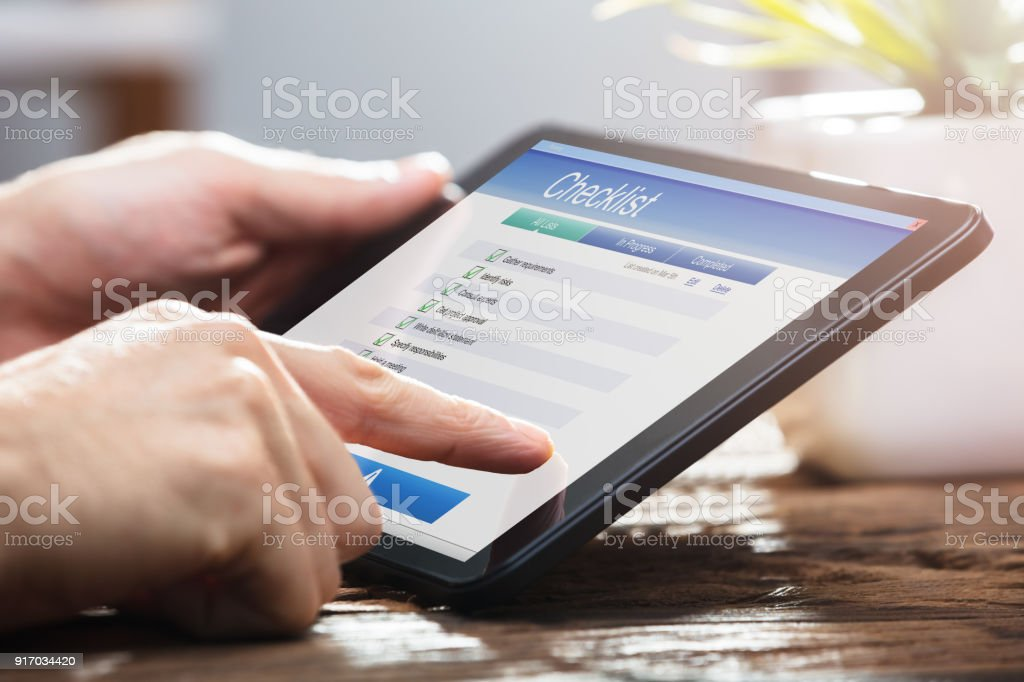 Businessperson Filling Checklist Form On Digital Tablet stock photo