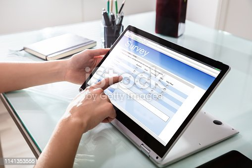 Close-up Of A Businessperson's Hand Filling Online Survey Form On Digital Laptop In Office