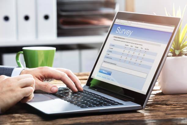 businessperson filling online survey form on laptop - perito foto e immagini stock